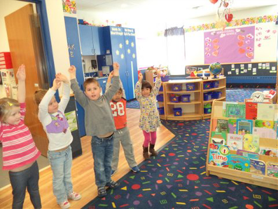 Spanish Immersion class raising arms in the air